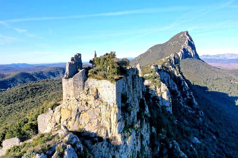 Photo de la montagne du pic saint loup vu de haut avec une ancienne ruine en premier plan et la montagne en arrière plan avec une face abrupte et rocheuse et l'autre en pente et avec de la verdure