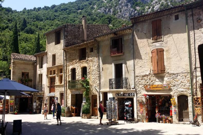 Place du village de saint guilhem le désert avec ses petits commerces et ses belles maisons en pierres