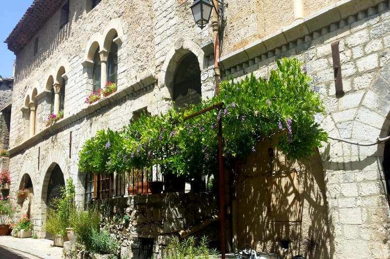 Grande façade en pierres d'une maison du village de saint guilhem le désert de style romane avec des ouvertures portes et fenêtres en arc de cercle