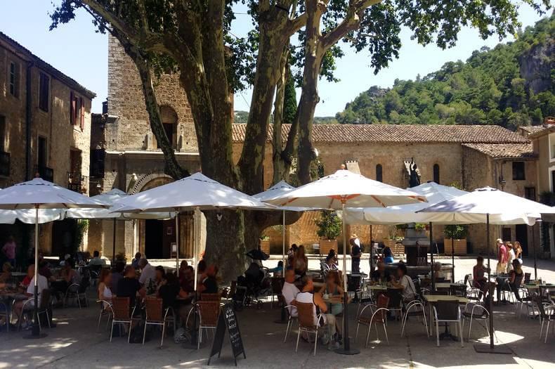 La place du village de saint guilhem le désert avec son magnifique et grand platane, sa fontaine, ses terrasses de café et restaurant et en fond l'entrée de l'abbaye de gellone