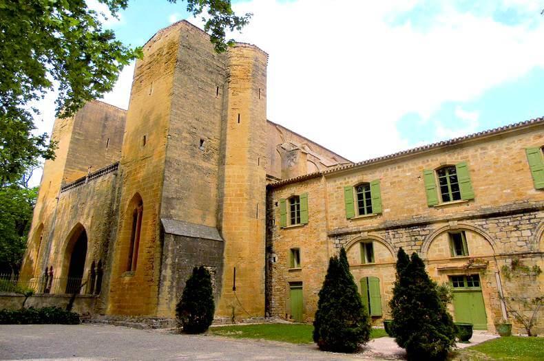 Devanture extérieure de l'abbaye de valmagne en pierre avec 2 grandes tours et des ouvrants avec des volets vert provence