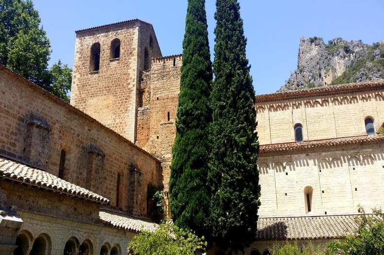 Vue de l'abbaye de gellone à l'intérieur du cloître avec deux grands arbres cyprès du sud et la belle construction en pierre
