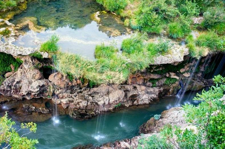 Cascade vue de haut avec l'eau qui coule d'un plan d'eau sur la roche dans le fleuve hérault de couleur émeraude
