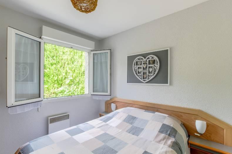 Chambre double avec lit double et fenêtre double vitrage ouverte. Tons blanc et bleu/gris.