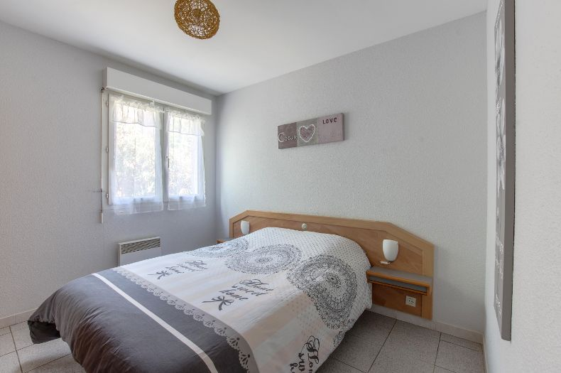 Chambre du gîte Coronille, décoration élégante et lumineuse. Lit double avec fenêtre.