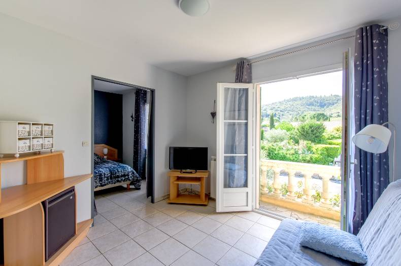 Séjour et chambre d'hôtes Garrigue avec deux pièces. Canapé, télévision, balcon et lit double.