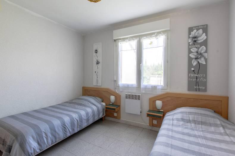 Chambre avec deux lits jumeaux et une fenêtre centrale double vitrage. Blanc, bleu/gris, bois.