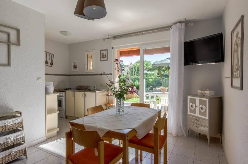 Salle à manger et cuisine du gîte Coronille. Table pour 4 personnes, kitchenette équipée et vue sur terrasse, jardin et piscine.