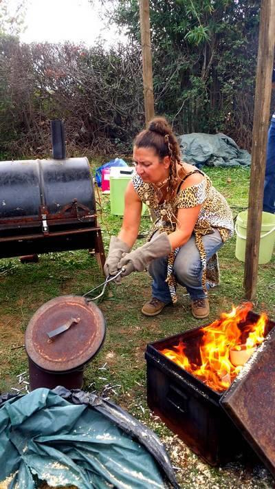 image d'une potière retirant les bols mis dans dans un récipient métallique avec de la sciure pour finir la cuisson lors du festibol de saint jean de fos