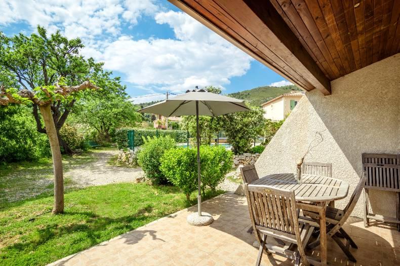 Vue depuis le gîte Cardabelle sur la terrasse et le jardin. Vue dégagée et paisible sur la propriété. Tables, chaises et parasol sur la terrasse ensoleillée.