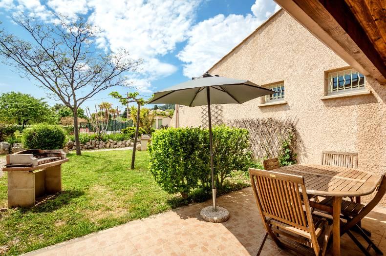 Terrasse du gîte Charmille avec vue dégagée sur un jardin. Table, chaises, parasol, barbecue.