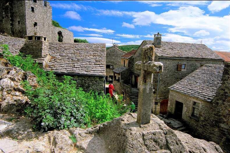 photo prise des toits des maisons du village de la couvertoirade et en premier plan une croix calvaire en pierre