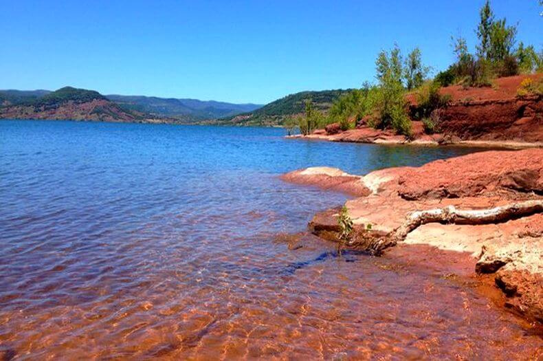image du lac du salagou avec une belle eau transparente et la roche du nom de ruffe est de couleur rouge