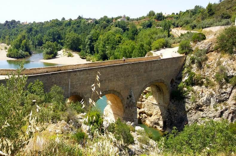 le pont du diable en pierre au dessus de l'hérault et au loin des plages pour pouvoir s'y baigner