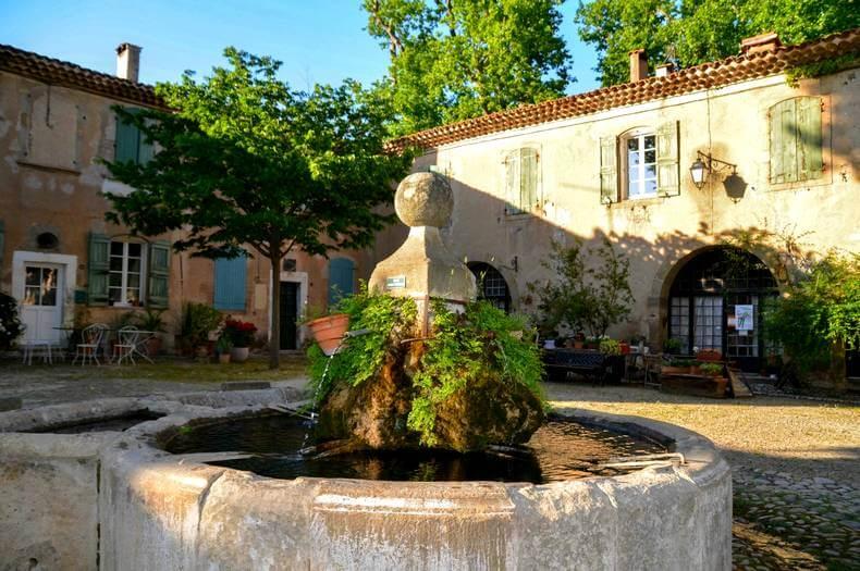 Place centrale avec la fontaine au centre et des habitations en fond de style provençale avec des volets vert