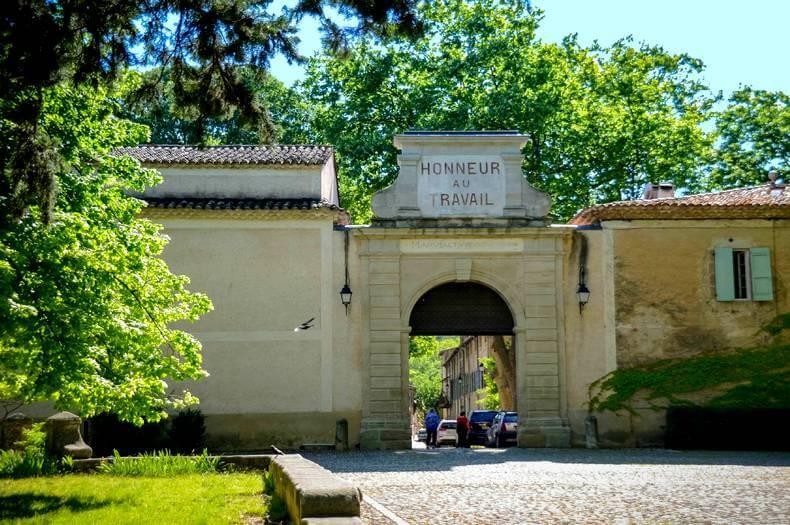 grand porche en pierre de l'entrée de la manufacture avec une inscription honneur au travail, pavés au sol et verdure