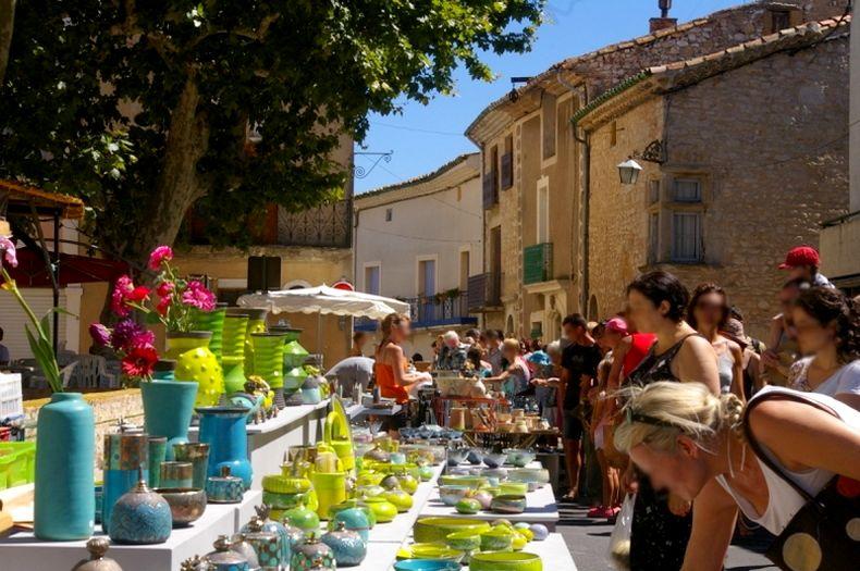 sur la place du village de saint jean de fos étales de poteries de différentes formes et couleurs et des personnes regardent et achètent