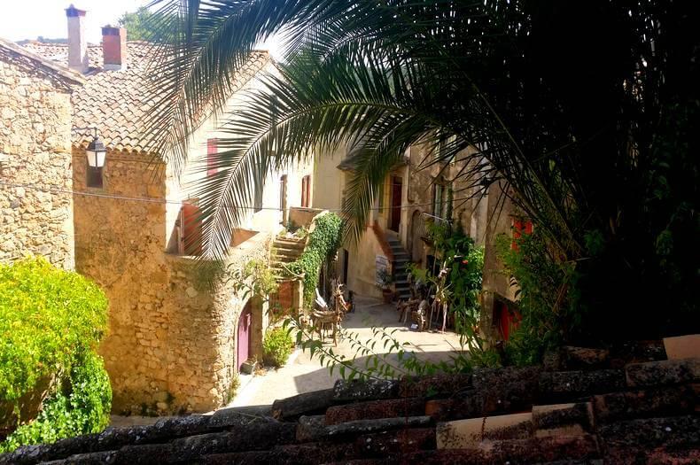 image de l'intérieur du village de mourèze avec de belles maisons en pierres et un palmier en premier plan