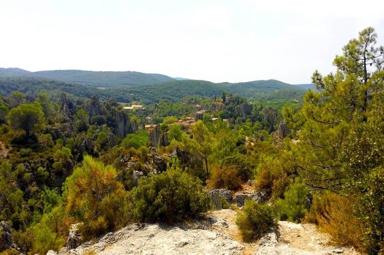 vue du village de mourèze en étant sur les hauteurs des collines du cirque de mourèze avec une belle végétation de sapins et de belles roches