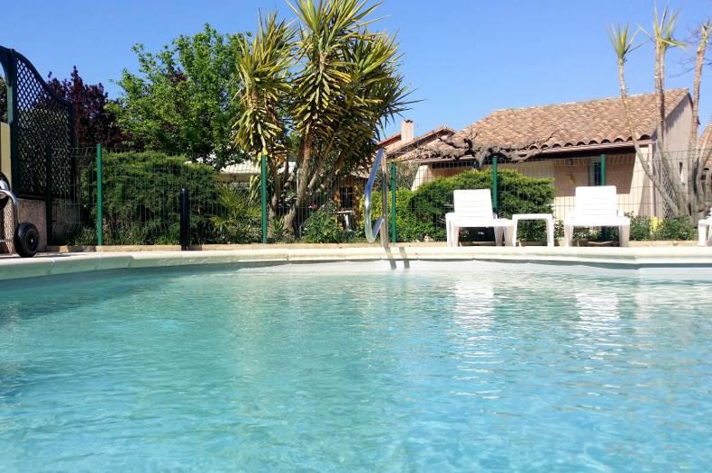 Photo prise dans la piscine avec vue sur le gîte Coronille situé en face, derrière le grillage de la zone de baignade. Eau transparente et soleil.