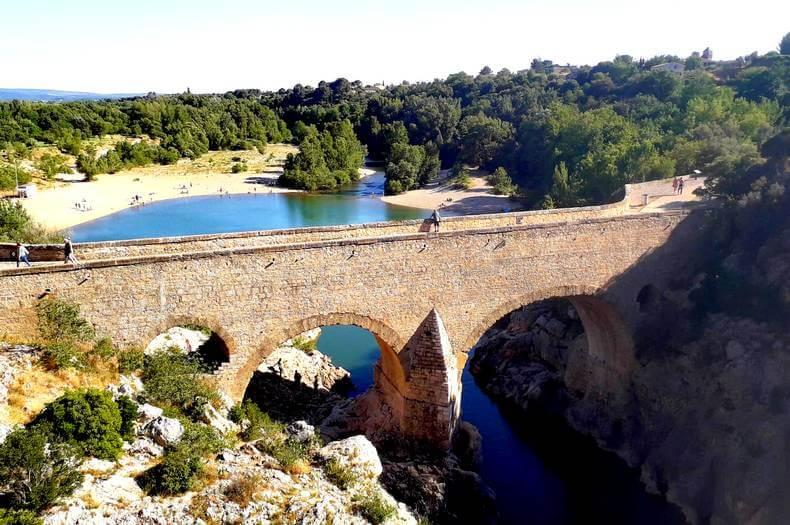 Pont du diable haut dessus du fleuve hérault avec des gens qui se promènent dessus et des gens au loin sur une plage au bord de l'eau