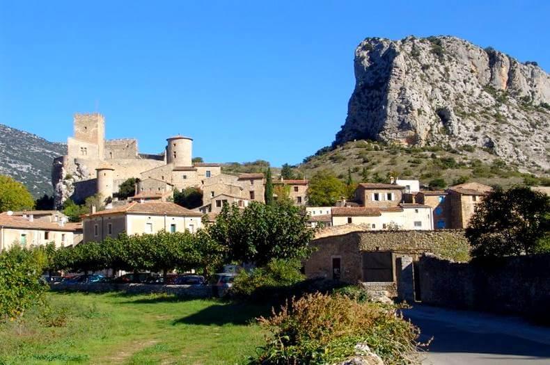 vue en arrivant au village en pierres de saint jean de buèges avec des tours le dominant et en arrière plan à droite un grand piton rocheux domine le village