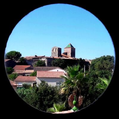 Vue du village de Saint Jean de Fos au travers d'un hublot rond avec le toit vernissé de l'église