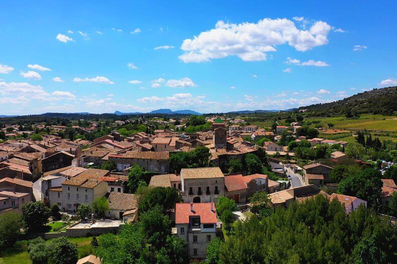Village de Saint Jean de Fos vue aérienne avec le ciel bleu les montagnes au loin et les toits des maisons