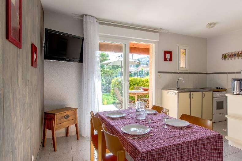 Salle à manger et cuisine équipée qui donnent sur une terrasse et jardin ensoleillés. Table et chaises à l