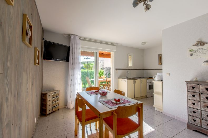 Salle à manger et cuisine du gîte charmille : 4 chaises, une table, une télé, une cuisine équipée et vue sur la terrasse et jardin ensoleillés.