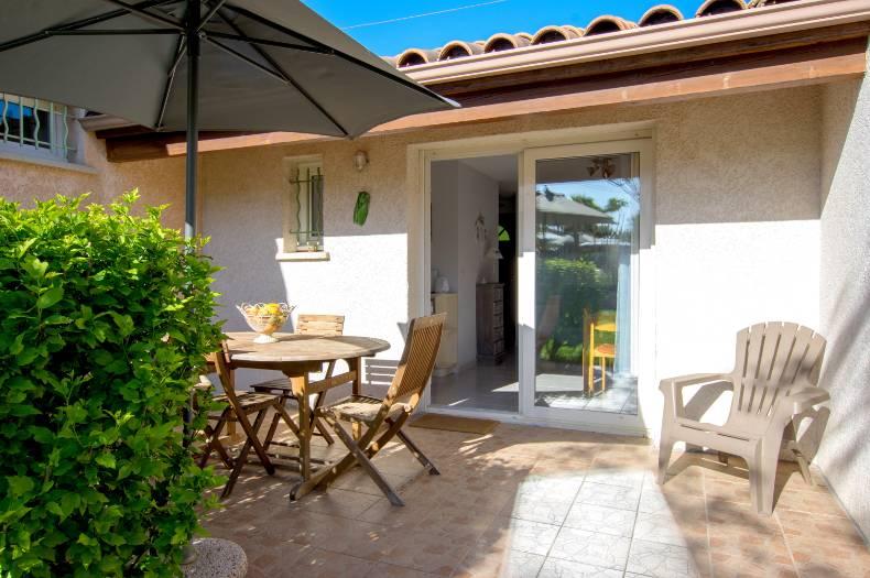 Terrasse et façade du gîte Charmille : haie verte, chaises et table en bois, parasol et vue sur le salon salle à manger du gîte par la porte-fenêtre double vitrage.