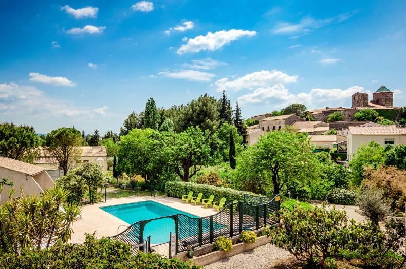 Vue du domaine de haut (depuis une des chambres). Vue sur les gîtes, la piscine et le village de Saint Jean de Fos. Verdure et soleil.